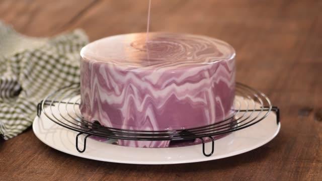nahaufnahme des professionellen kochs, der den glasurkuchen bedeckt. frau dekoriert kuchen mit verspiegelter glasur - küchenzubehör stock-videos und b-roll-filmmaterial