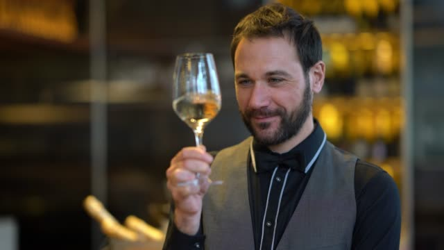 Close up of professional wine taster tasting white wine looking at the color and smelling the served wine Close up of professional wine taster tasting white wine looking at the color and smelling the served wine in a wineglass tasting stock videos & royalty-free footage