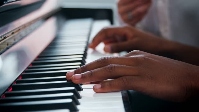 vídeos de stock e filmes b-roll de close up of pupil with teacher playing piano in music lesson - instrumento musical