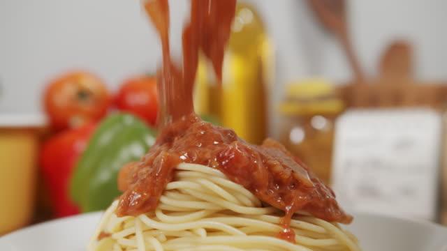 vidéos et rushes de fermez-vous vers le haut de mettre la sauce de viande sur des spaghettis, les pâtes sur une plaque. spaghetti maison et concept de cuisine. - spaghetti bolognaise