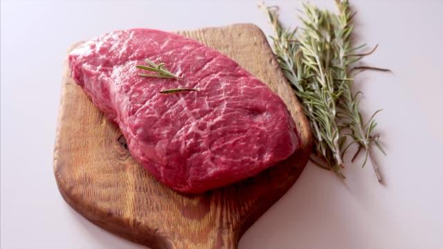 nahaufnahme von roh-frischsteak serviert mit rosmarin auf rustikalen holzbrett - steak stock-videos und b-roll-filmmaterial