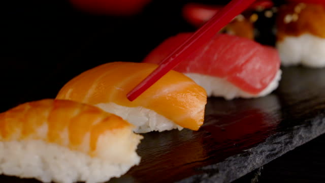 close up of red chopsticks taking portion of sushi roll on the table restaurant video