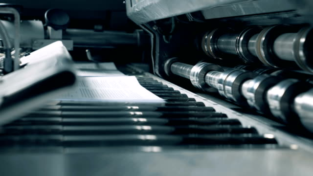 close up of rolling mechanism issuing paper pages - attrezzatura industriale video stock e b–roll