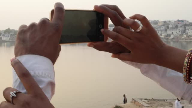 Close up of romantic couple taking photos on a mobile phone camera Pushkar, Rajasthan, india video
