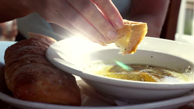 close up of rosemary bread dipped in olive oil with pesto in winery - immergere video stock e b–roll