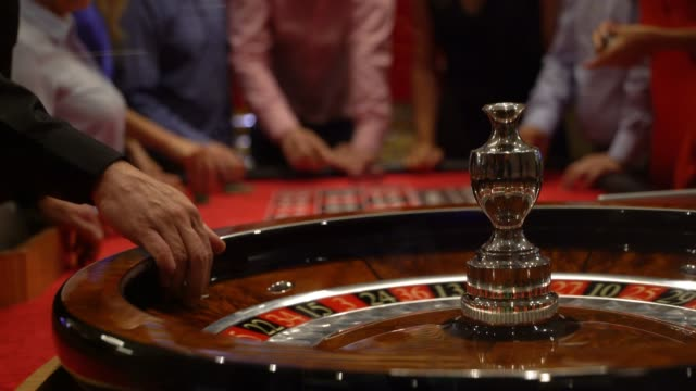 Close up of roulette spinning while people are placing bets at the background