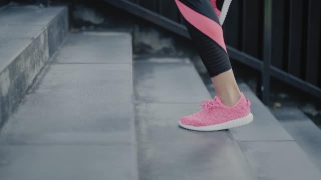 vidéos et rushes de fermez-vous vers le haut du coureur dans la ville - joggeuse