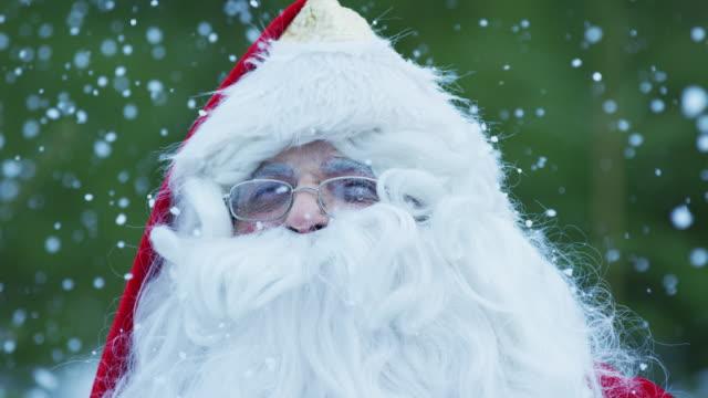 vídeos de stock e filmes b-roll de close up of santa claus admiring the snowfall - man admires forest