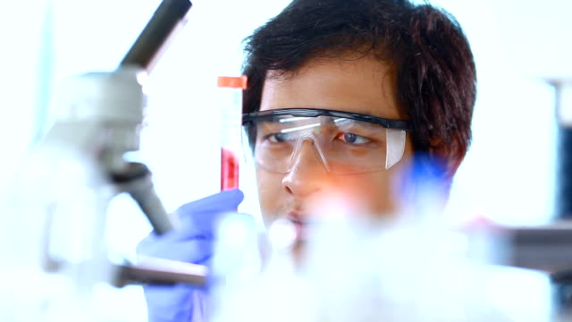 close up of scientist looking and shaking a round bottom flask liquid in laboratory video