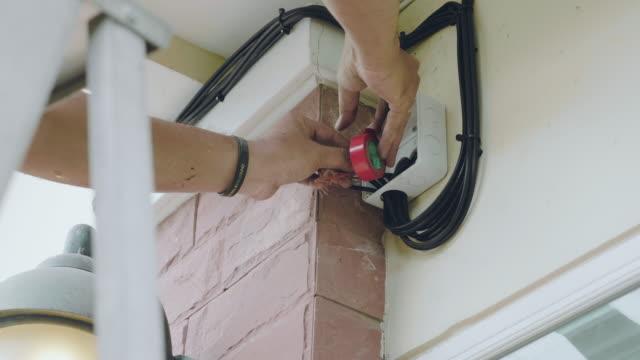 vídeos y material grabado en eventos de stock de close up de consultor de seguridad, instalación cctv cámara a la pared de la casa - descarga eléctrica