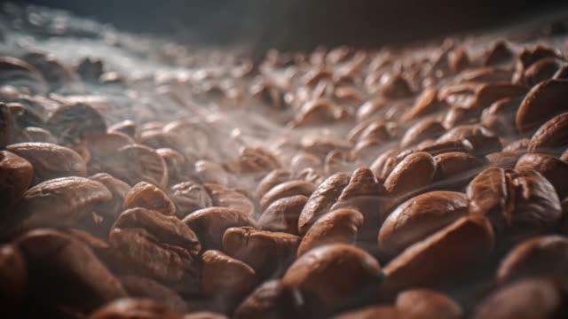 nahaufnahme von samen von kaffee. duftende kaffeebohnen sind gerösteter rauch kommt aus kaffeebohnen. - cafe stock-videos und b-roll-filmmaterial