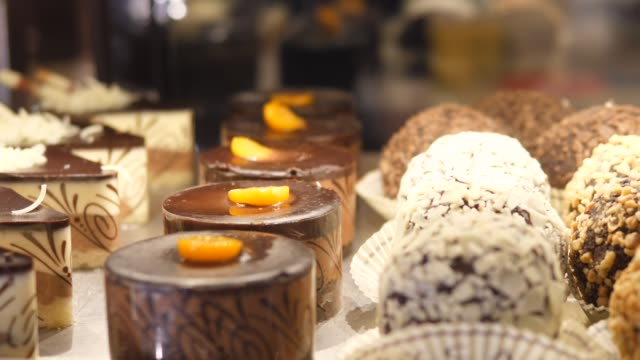 Close up of selection of chocolate cakes on a display in confectionery shop
