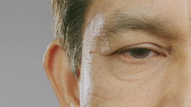 close up of senior man eye, slowly open right eyes. asian man, macro shot. copy space. - веко стоковые видео и кадры b-roll
