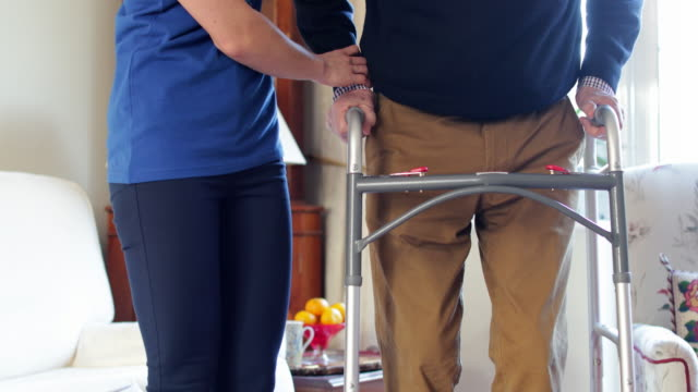 Close Up Of Senior Man With Hands On Walking Frame Being Helped By Care Worker Close Up Of Senior Man With Hands On Walking Frame Being Helped By Care Worker sociology stock videos & royalty-free footage