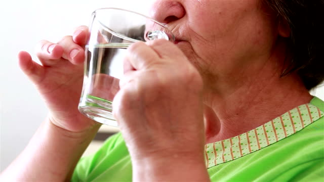 Close up of senior woman taking a pill video