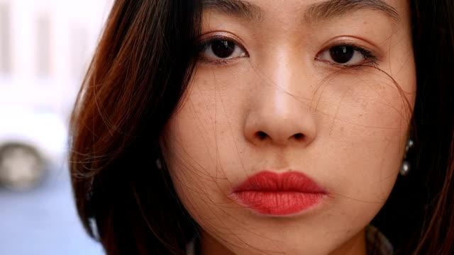 stockvideo's en b-roll-footage met close up van ernstige schattig aziatische vrouw gezicht - buiten - portait background