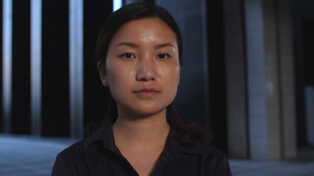 stockvideo's en b-roll-footage met close up van ernstige jonge chinese vrouw in slow motion, 4k - portait background
