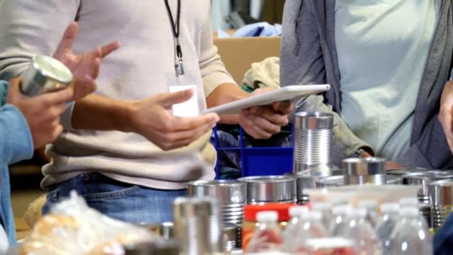 vídeos y material grabado en eventos de stock de cerca de varios voluntarios de pie alrededor de una mesa de suministros para empacar para la recolección de alimentos - food drive