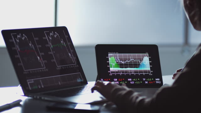 Close Up Of Share Trader At Desk With Stock Price Data Displayed On Laptop And Digital Tablet Close up of share trader at desk with stock price data displayed on laptop and digital tablet - shot in slow motion trading stock videos & royalty-free footage