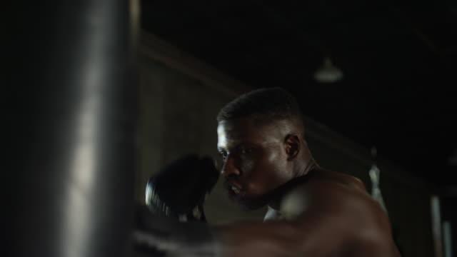 primo tempo di un afroamericano senza camicia che colpisce una borsa pesante nella palestra mma - sacco per il pugilato video stock e b–roll