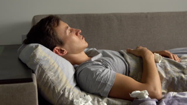 close up of sick young man is coughing asleep in bed - guy sofa video stock e b–roll