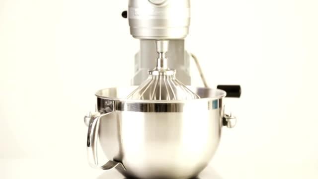 vidéos et rushes de gros plan de mélangeur électrique alimentaire argenté sur un fond blanc. - batteur électrique