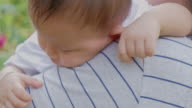 istock Close up of sleeping baby on mother shoulder in garden. Asian people. 1209606494