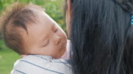 istock Close up of sleeping baby on mother shoulder in garden in slow motion with sun ray, orbit shot. Asian people. 1209590784