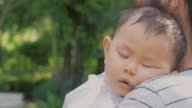 istock Close up of sleeping baby on mother shoulder walking in garden. Asian people. 1209604153