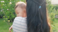 istock Close up of sleeping baby on mother shoulder walking in garden in slow motion with sun ray, orbit shot. Asian people. 1209594893