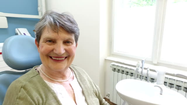 Close up of smiling elderly female patient at dentist video