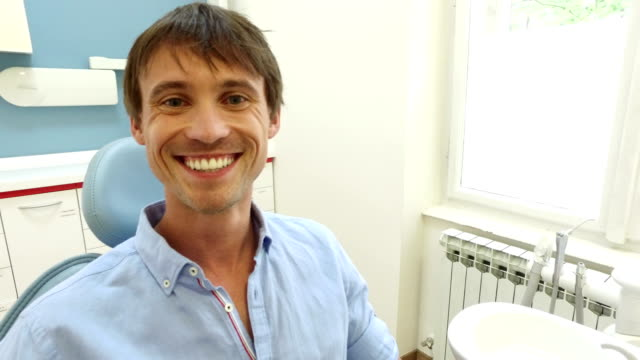 Close up of smiling man with healthy white teeth at dentist video