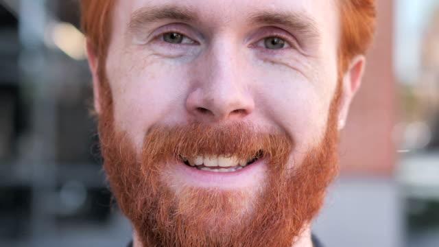 close up of  smiling redhead beard young man face - rude włosy filmów i materiałów b-roll