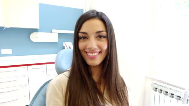 Close up of smiling woman looking at camera while sitting in the dental chair video