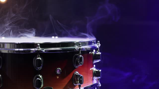 Close up of snare drum with smoke in the dark with beautiful lighting.