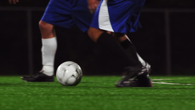 Close up of soccer players kicking a ball down the field video