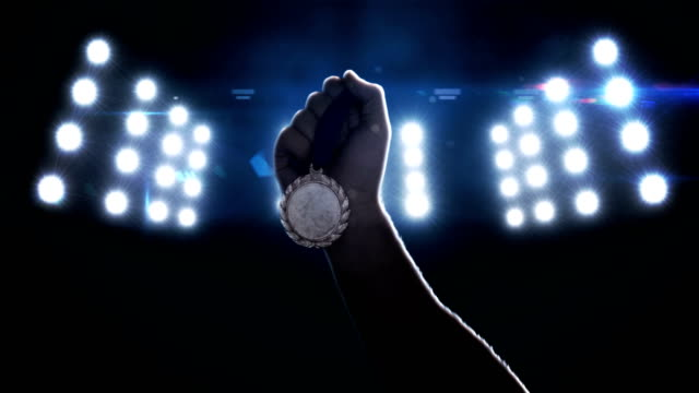 Close up of sportsman hand holding a medal video