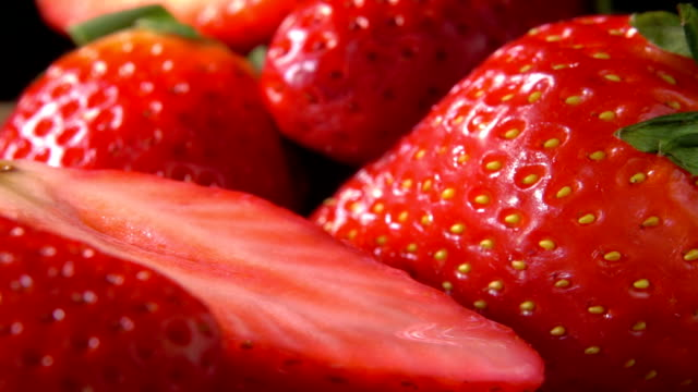 Close up of strawberry slice falling on berries - video