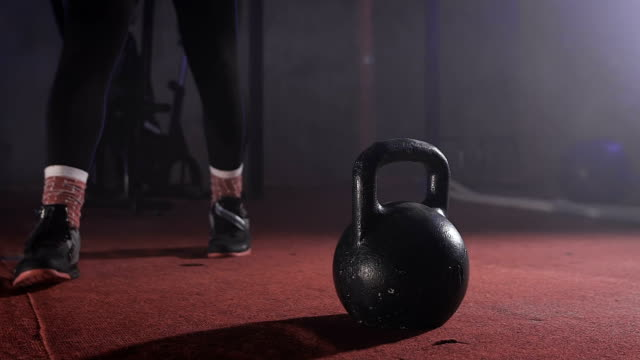 Close up of strong man in training suit going to the kettlebell and taking it with both hands and lifting it slow motion video