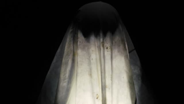 Close up of supernatural force act or power performed by a human earing white colored cloak coverings his whole body at night time at a place haunted by witches and wizards.