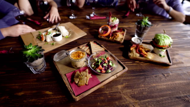 Close up of table served with assorted food setting on wooden platters. Image of different dishes and snacks on the brown surface with people and glasses of wine in the background video