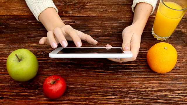 Close up of tablet screen with fruits on the table