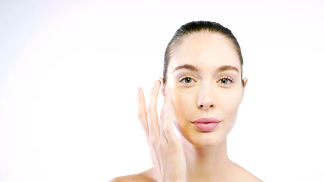 close up of the face of a beautiful woman with perfect skin thanks to creams to keep young and cream contour anti-aging and wrinkle eyes. - skóra część ciała filmów i materiałów b-roll