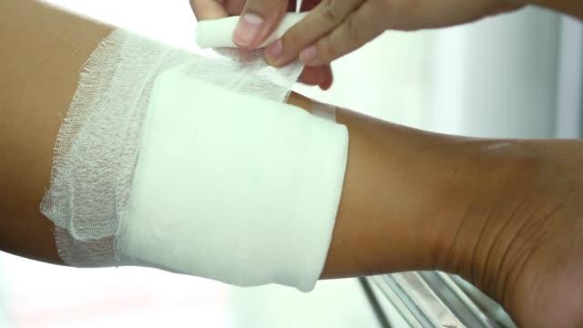 pansuman yapmak için gazlı bez tutan elin yakın ve yarakapatmak için, enfeksiyonu önlemek. - gazlı bez stok videoları ve detay görüntü çekimi