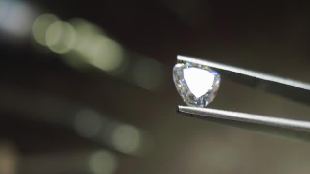 chiudi le mani di un orafo mentre lavora su un anello di diamanti. - brillante video stock e b–roll