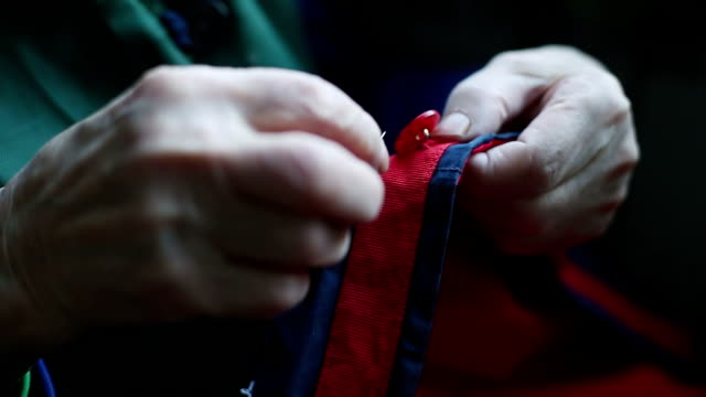 Close up of the hands of a very old woman sew on buttons. video