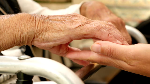 Close up of the hands of an old woman on a crutch, hands of a young woman petting them Close up of the hands of an old woman on a crutch, hands of a young woman petting them crutch stock videos & royalty-free footage