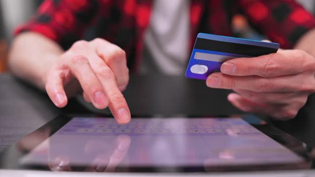 zbliżenie rąk nastoletniego mężczyzny. jedna ręka trzyma kartę, a druga wpisuje numer karty kredytowej na klawiaturze tabletu. młody mężczyzna siedzi przy biurku w jasnym pokoju - data filmów i materiałów b-roll