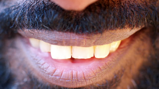 vídeos de stock e filmes b-roll de close up of the mouth and teeth of a smiling black man - mouth
