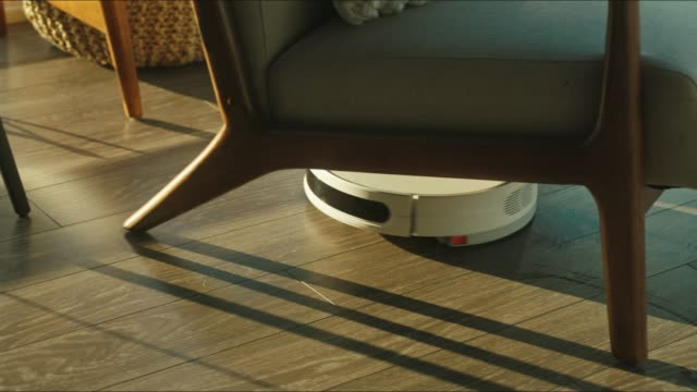 Close up of the robotic vacuum cleaner riding around and cleaning up apartments Close up of the robotic vacuum cleaner riding around and cleaning up apartments, future in the house, using modern technologies in everyday life, routine tasks, cleaning messy floor in the kitchen appliance stock videos & royalty-free footage